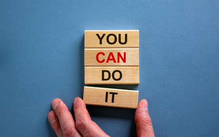 Male hand placing a block with word 'it' on a blocks tower with words 'you can do it'. Beautiful blue background. Copy space.