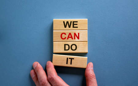 Male hand placing a block with word 'it' on a blocks tower with words 'we can do it'. Beautiful blue background. Copy space.
