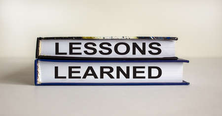 Books with text 'lessons learned' on beautiful white table. White background. Business concept.