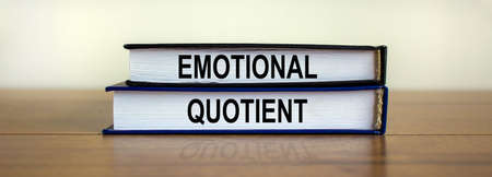 Books with text 'emotional quotient' on beautiful wooden table. White background. Business concept.