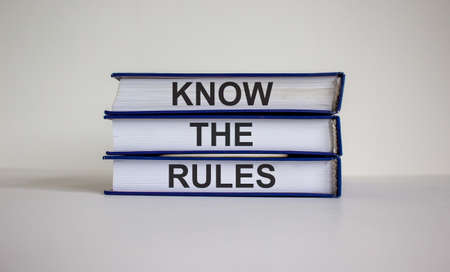 Books with text 'know the rules' on beautiful white table. White background. Business concept. Copy space. 免版税图像