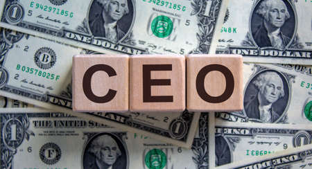 Concept word 'CEO' on cubes on a beautiful background from dollar bills. Business concept.