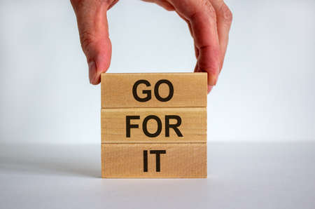 Male hand placing a block with word 'go' on top of a blocks tower with words 'go for it'. White table. Beautiful white background. Copy space. Business concept.
