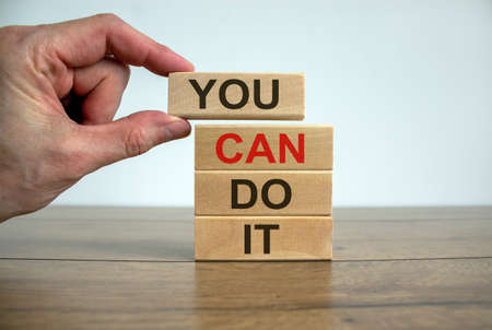 Male hand placing a block with word 'you' on top of a blocks tower with words 'you can do it'. Wooden table. Beautiful white background. Copy space. 免版税图像