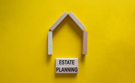 Model of a wooden house. Words 'estate planning' on wooden blocks. Copy space. Business concept. Beautiful yelllow background.