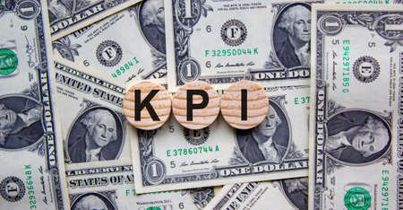 Concept word 'KPI' on circles on a beautiful background from dollar bills. Business concept.