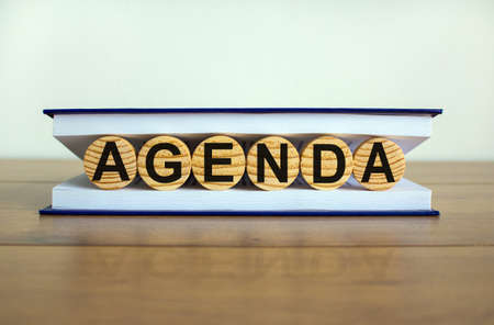 Concept word 'agenda' on wooden circles between pages of a book on a beautiful wooden table. White background. Business concept.