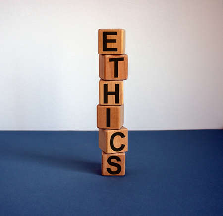 Wooden cubes form the word 'ethics' on blue table. Beautiful white background, copy space. 免版税图像