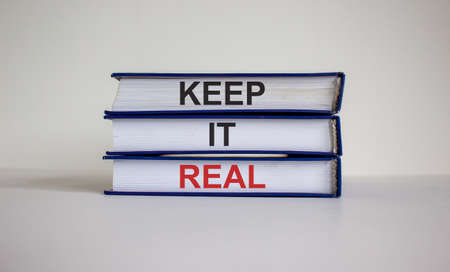 Books with text 'keep it real' on beautiful white table. White background. Business concept.