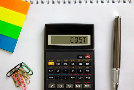 Calculator with inscription 'cost', white note, colored paper, paper clips, pen. Business concept.