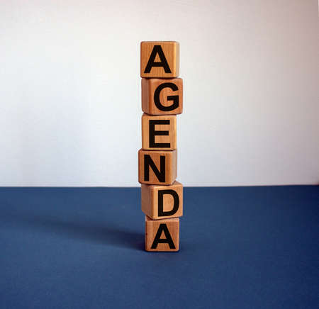 Wooden cubes form the word 'agenda' on blue table. Beautiful white background, copy space.
