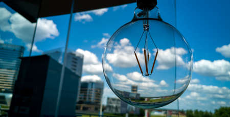 Round glass light bulb on a background of blue sky with clouds. Concept image. 免版税图像