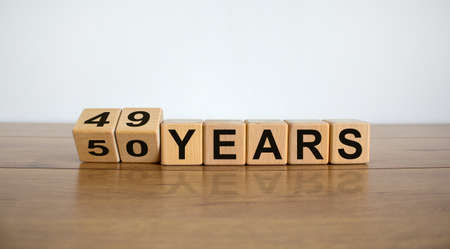 Turned cubes and changed the expression '49 years 'to '50 years' or vice versa. Beautiful wooden table, white background. Business concept, copy space.
