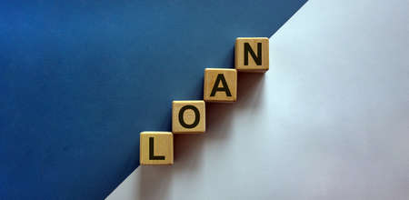 Wood block with word 'loan' stacking as step stair on paper blue and white background, copy space. Business concept success process.