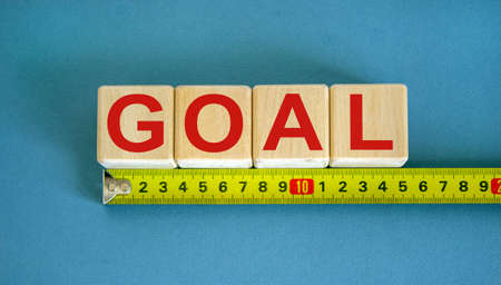 'Goal' word on cubes arranged behind the ruler on beautiful blue background. Business concept.