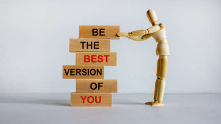 Concept of building success foundation. Wooden blocks on the stack of wooden blocks. Wooden model of human. Text 'be the best version of you'. Beautiful white background, copy space. 免版税图像