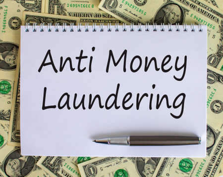 White note with 'Anti money laundering' text on beautiful background from dollar bills and metalic pen. Business concept.