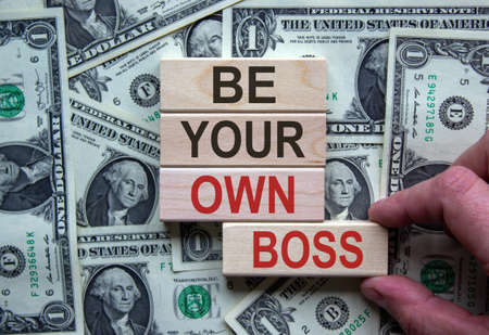 Wooden blocks form the words 'be your own boss' on beautiful background from dollar bills. Male hand. Business concept. Copy space.