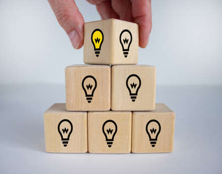 Leader with idea and innovation. Man hand flips cube with icon light bulb. Business concept.