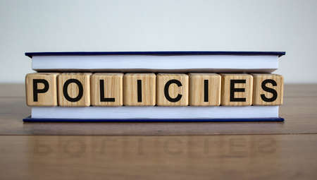 Concept word 'policies' on wooden cubes between pages of a book on a beautiful wooden table. White background. Business concept.