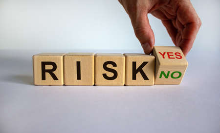 Hand is turning a cube and changes the word 'no' to 'yes' or vice versa. Word 'risk'. Beautiful white background, copy space. Business concept.