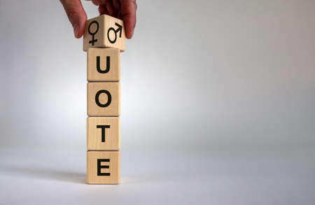 Hand is turning a cube and changes the word 'quote' with male sign to female sign or vice versa. Beautiful white background, copy space. Business concept.