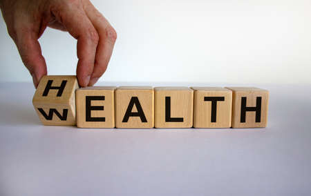 Hand is turning a cubes and changes the word 'health' to 'wealth' or vice versa. Beautiful white background, copy space. Business concept. 免版税图像