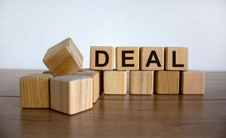 Concept word 'deal' on cubes on a beautiful wooden table. White background. Business concept. Copy space. 免版税图像