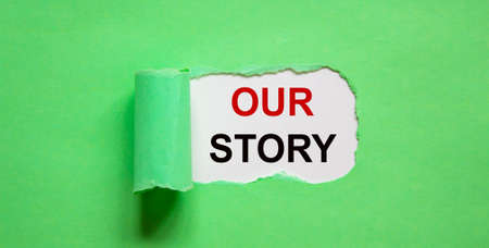 The text 'our story' appearing behind torn green paper. Business concept.