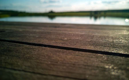 Old wooden board close-up. In the background a blurred lake and sky.