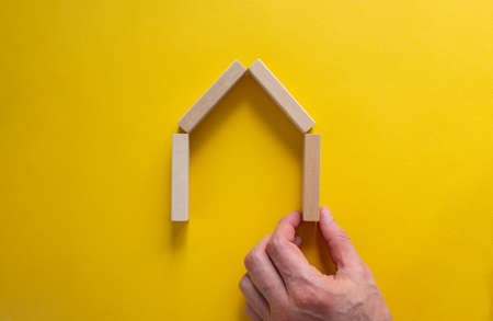 Male hand builds a model of a wooden house from wooden blocks. Copy space. Business concept. Beautiful yellow background.