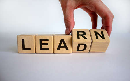 Hand is turning a cubes and changes the word 'learn' to 'lead' or vice versa. Beautiful white background, copy space. Business concept.