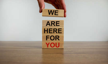 Concept of building success foundation. Men hand put wooden blocks on the stack of wooden blocks. Text 'we are here for you'. Beautiful white background, copy space.