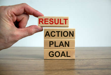 Wooden blocks form the words 'goal, plan, action, result' on wooden table, beautiful white background. Male hand. Business concept. Copy space.
