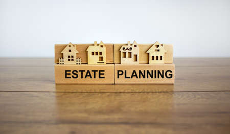 Wooden blocks form the words 'estate planning', miniature house, wooden table. Beautiful white background, copy space. Business concept. Banco de Imagens