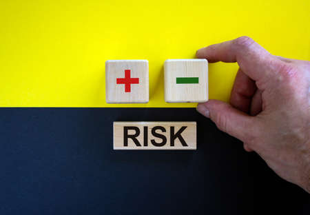 Businessman holds a cubes with minus icon. Wooden cubes with word 'risk'. Beautiful yellow and black background. Copy space. Business concept.