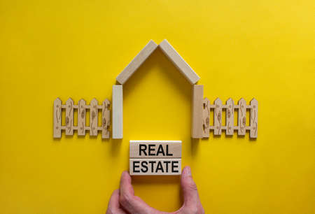 Model of a wooden house. Words 'real estate' on wooden blocks. Male hand, wooden fence. Copy space. Business concept. Beautiful yelllow background. Banco de Imagens