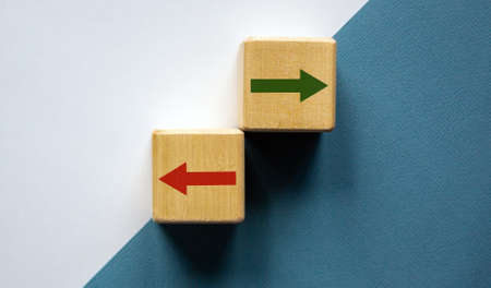 Conceptual image of choice and direction. Wooden cubes with arrows pointing in opposite directions. Beautiful white and blue background, copy space.