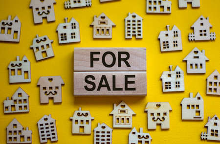 Wooden blocks form the words 'for sale', miniature wooden houses. Beautiful yellow background, copy space. Business concept.