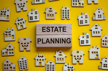 Wooden blocks form the words 'estate planning', miniature wooden houses. Beautiful yellow background, copy space. Business concept. Stock fotó