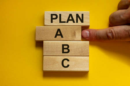 Time to Plan A. Wooden blocks form the words 'plan, A, B, C,' on yellow background. Male hand. Beautiful background. Business concept.