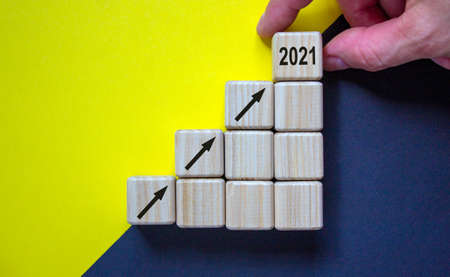 Wood cubes with arrows sign and number 2021 stacking as step stair on paper black and yellow background, copy space. Male hand. Business concept of 2021 year.