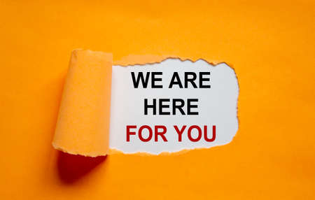 The text 'we are here for you' appearing behind torn orange paper. Business concept. Copy space.