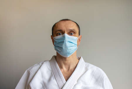 A young strong man in a white kimono for sambo, jiu jitsu and other martial arts with a blue medical mask. COVID-19 Pandemic Coronavirus concept.