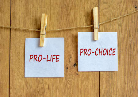 Wooden clothespins with white sheets of paper. Text 'pro-life, pro-choice'. Beautiful wooden background. Female right on abortion concept, copy space.