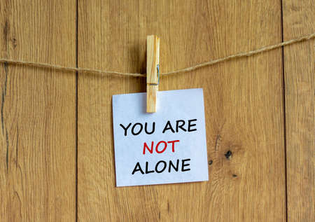Wooden clothespin with white sheet of paper. Text 'you are not alone'. Beautiful wooden background. Business concept, copy space.