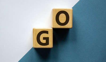 Conceptual image of motivation. Wooden cubes with word 'go'. Beautiful white and blue background, copy space.