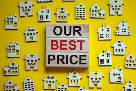 Wooden blocks form the words 'our best price', miniature wooden houses. Beautiful yellow background, copy space. Business concept. Banco de Imagens