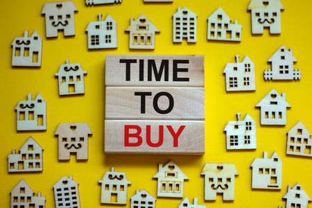 Wooden blocks form the words 'time to buy', miniature wooden houses. Beautiful yellow background, copy space. Business concept.