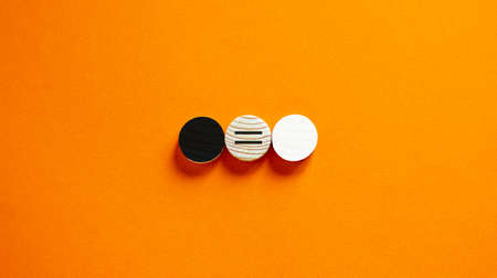 Racial equality concept. Black and white wood circles on beautiful orange background. Copy space.